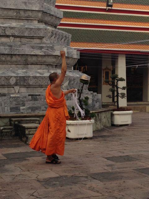 O monge contruindo uma teia de energia no barbante!